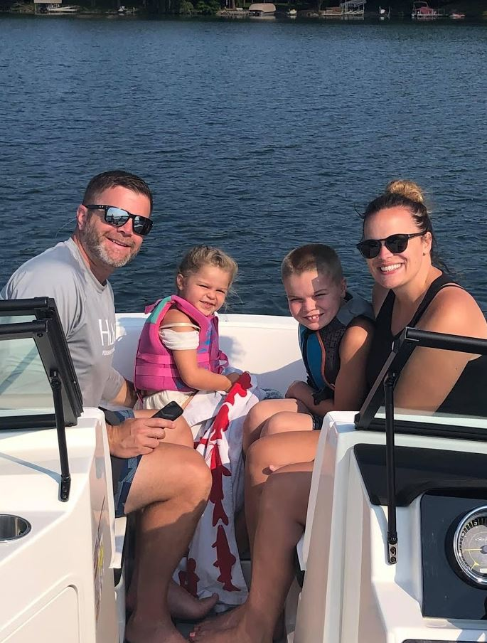 Mitch Frydrych with his young children and wife on a boat.